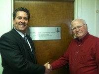 Cayuga Radio Group VP/GM Chet Osadchey, left, dedicates the cluster's conference room to Rudy Paolangeli. [Click for 2012 story]